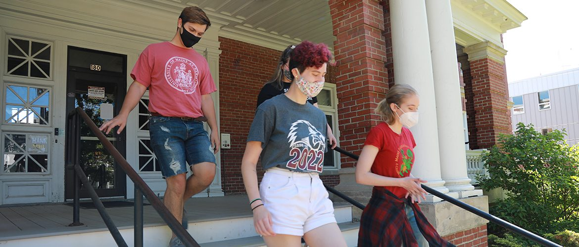 Students leaving residence hall in masks