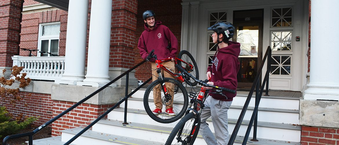 Students leaving Purington Hall residence hall with mountain bikes
