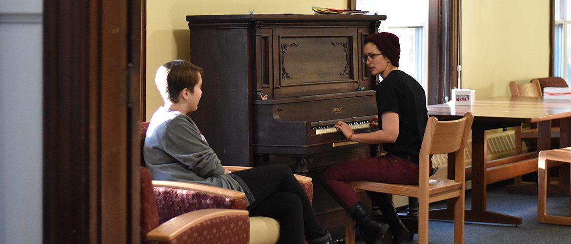 Students playing piano in Purington Hall common area