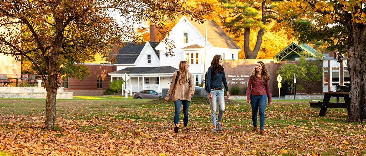 Three students walking across campus in fall