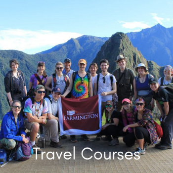 A group photo of UMF students holding the UMF banner with Machu Picchu behind them.