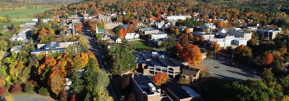 Aerial view of campus buildings, trees, and mountains