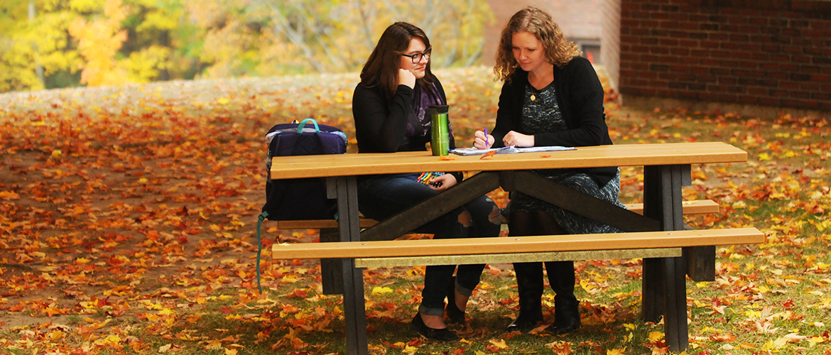 Students sitting at a picnic table.