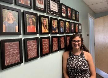 A student stands a wall of portraits.