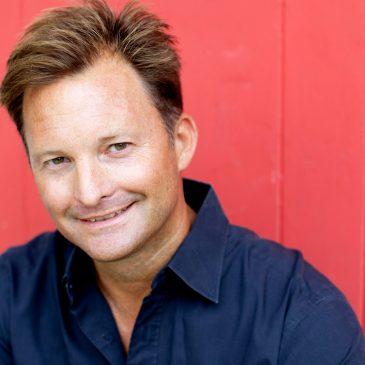 Christopher Bakken smiling in front of red backdrop
