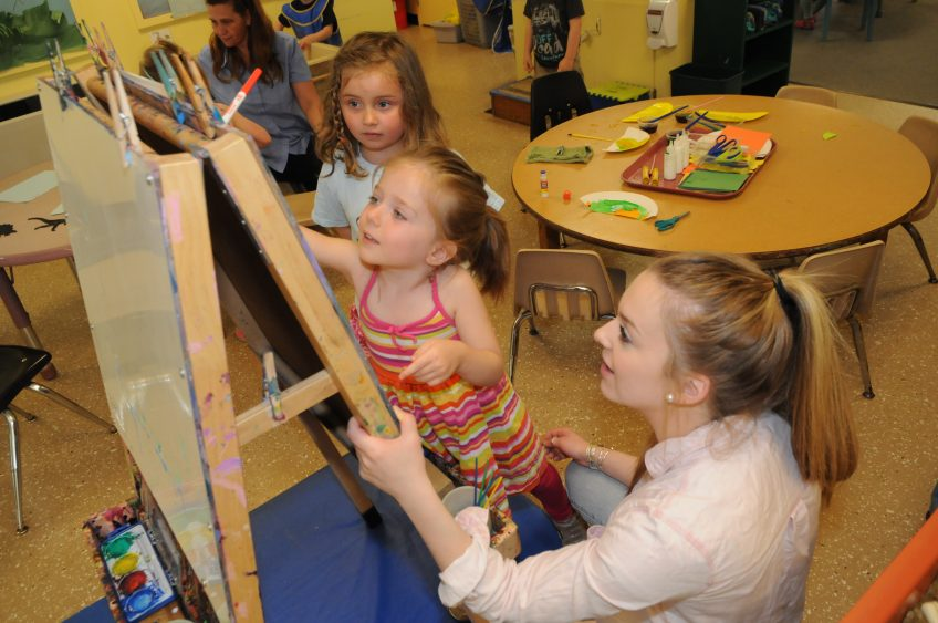 Student working with young children in Sweatt-Winter Childcare Center