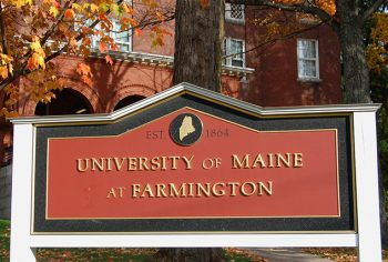 Closeup of University sign in front of Merrill Hall