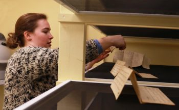 Madeline Soucie examining original source documents at the Maine State Archives.