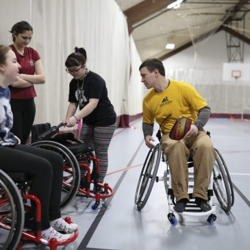 Brandon Merry '15, senior program manager at Maine Adaptive Sports & Recreation in Newry, instructs students on how to use sport chairs prior to playing a game of wheelchair pickleball in UMF's Fitness and Recreation Center.