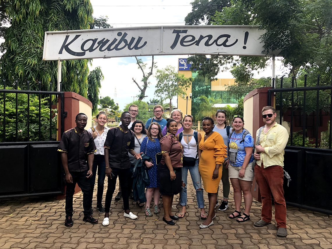 "UMF students and faculty leaders with local staff outside Kilimanjaro Café in Moshi in Northern Tanzania. Sign reads ""Come Back Again."""