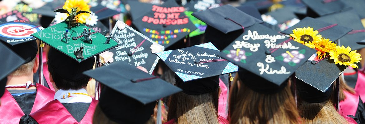 Students' decorated mortarboards at commencement
