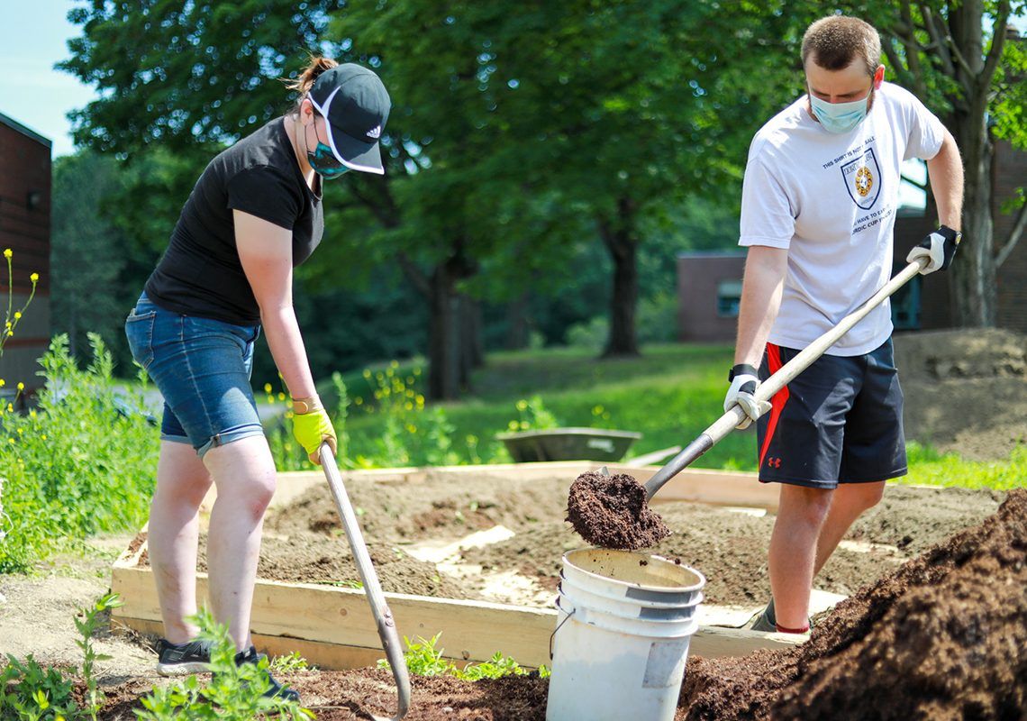 Left to right: Sara Taylor and James Cooke, UMF work-initiative students, helped create campus raised beds in addition to creating short videos and online drawings of the garden creation process.