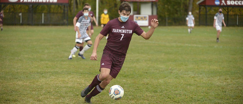 Men's soccer player kicking soccer ball