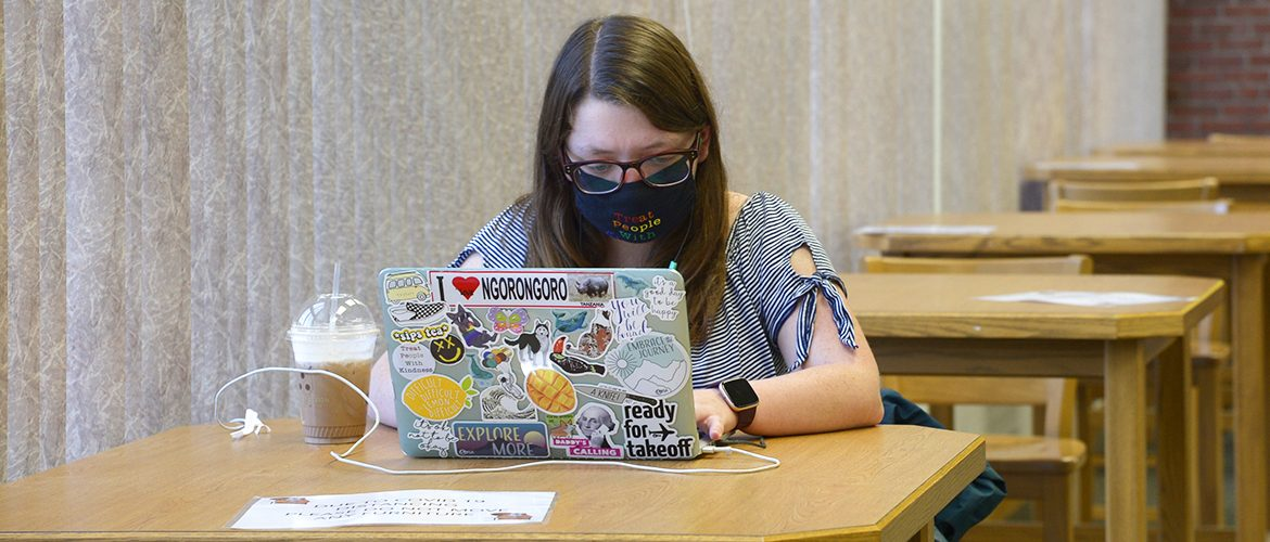 Student wearing a mask working on a laptop