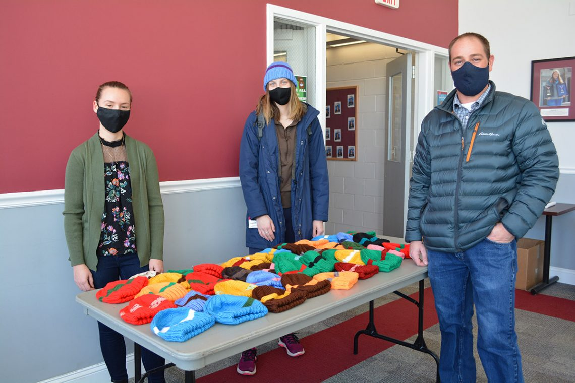 (Left to right) Brianna Hinkley, UMF senior from Kingfield and Peer Care Manager at UMF Covid Testing sight helps Page Brown, UMF senior from Boothbay, select her favorite hat from a huge assortment, with Keenan Farwell, director of UMF Facilities Management.
