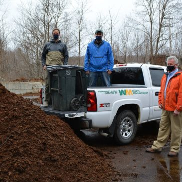 Luke Kellett and Mark Pires, former and current UMF sustainability coordinators, and Jeff McGown, a senior district manager with Waste Management, bring donated truck to site of UMF compost initiative.
